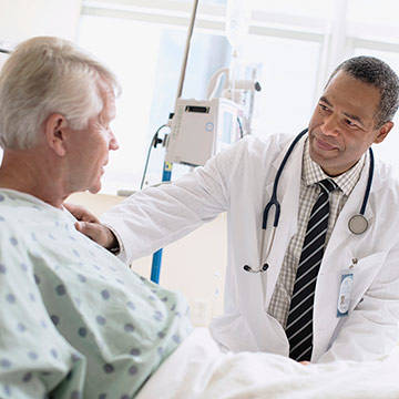 doctor visiting man in hospital bed