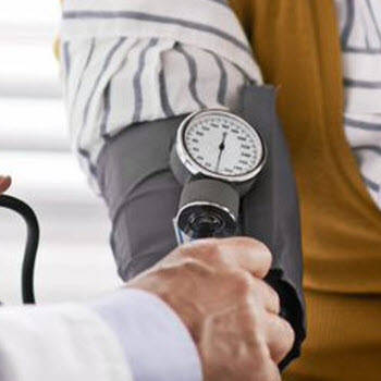 Blood pressure cuff on woman's arm