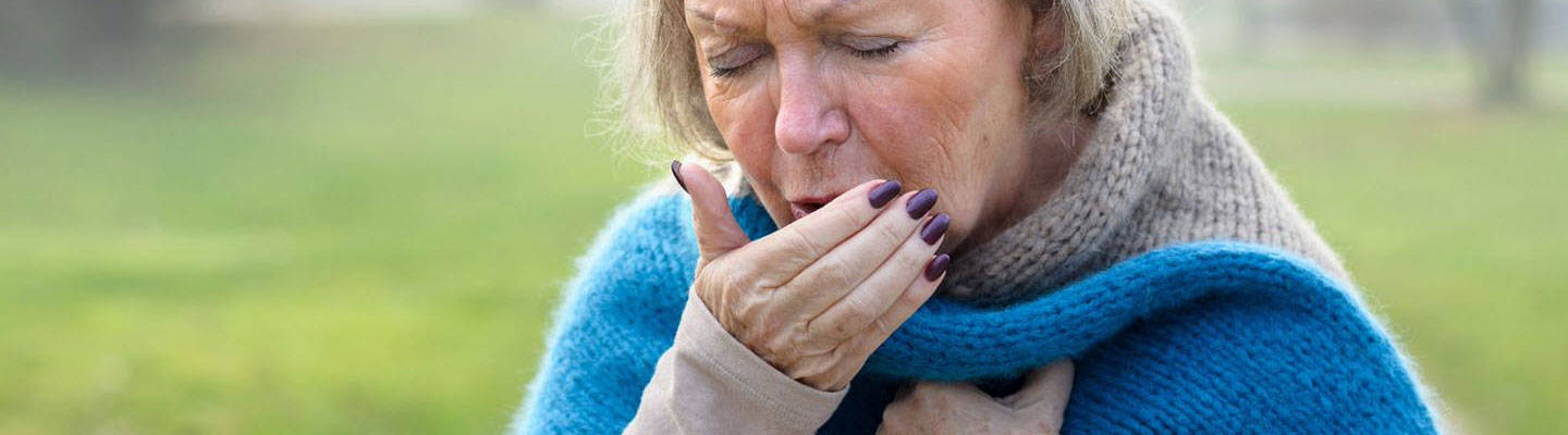 Older woman coughing into hand