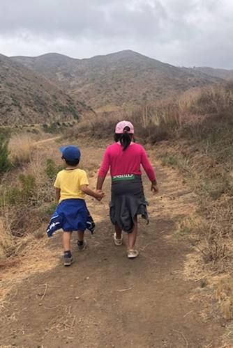 Brother and sister holding hands while walking on trail