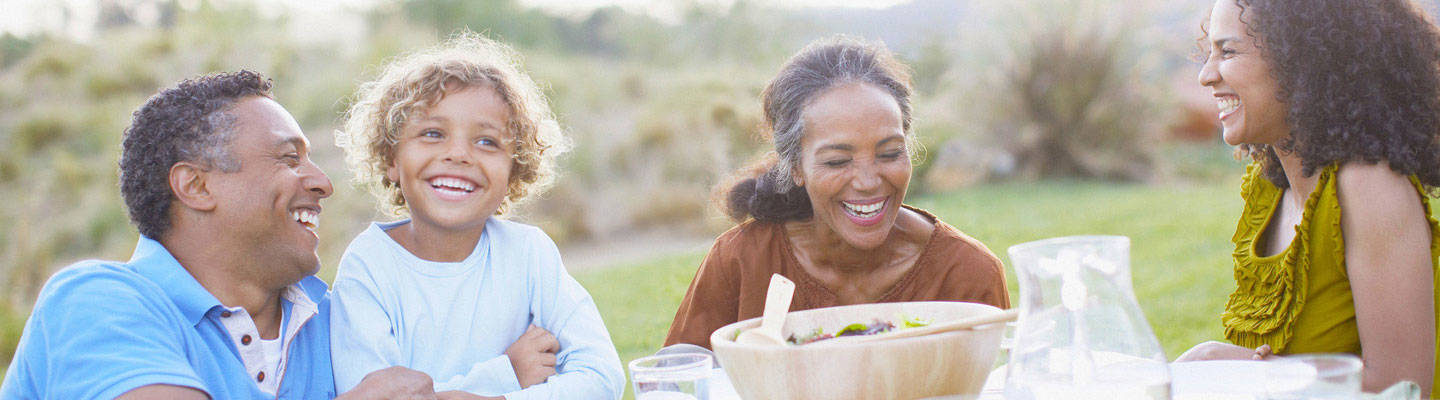 Family smiling at outdoor picnic