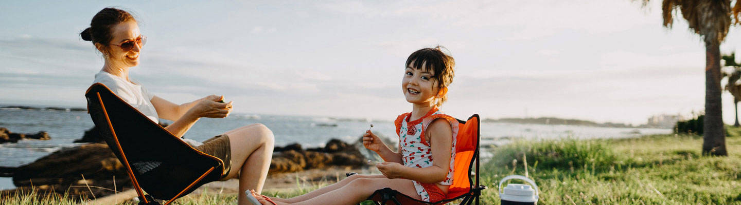 Mother and daughter sitting on lawn chair at beach