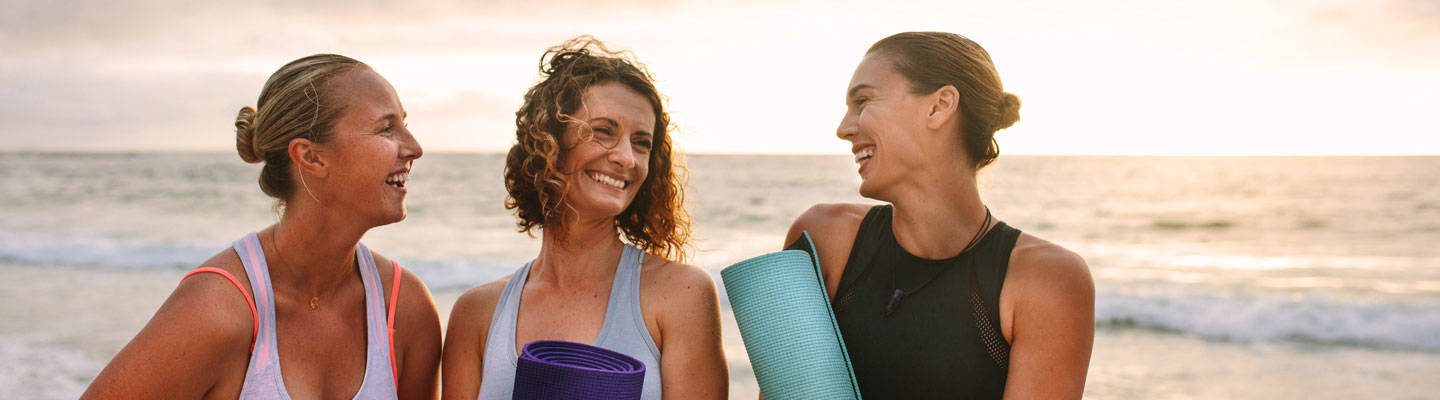 3 women carrying  yoga mat at beach