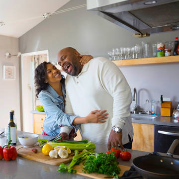Couple smiling while preparing meal