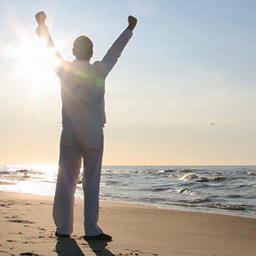 Man on beach arms raised