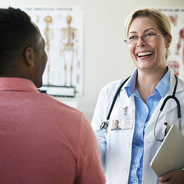 Doctor smiling at patient in exam room