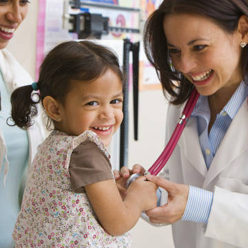 Doctor showing a stethoscope to a little girl