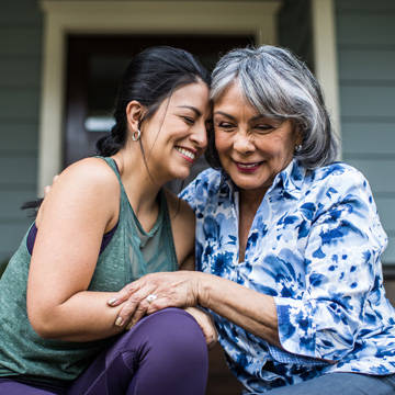Grown woman hugging older mother in front of house