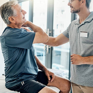 Physical therapist evaluating patient's shoulder