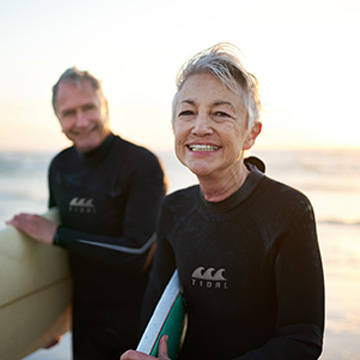 Middle age couple wearing wet suits and carrying surfboards