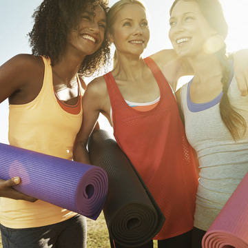Women smiling with yoga mats