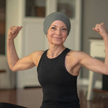 Woman with cancer flexing in yoga studio