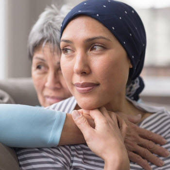 Asian woman in her 60s comforting friend with cancer