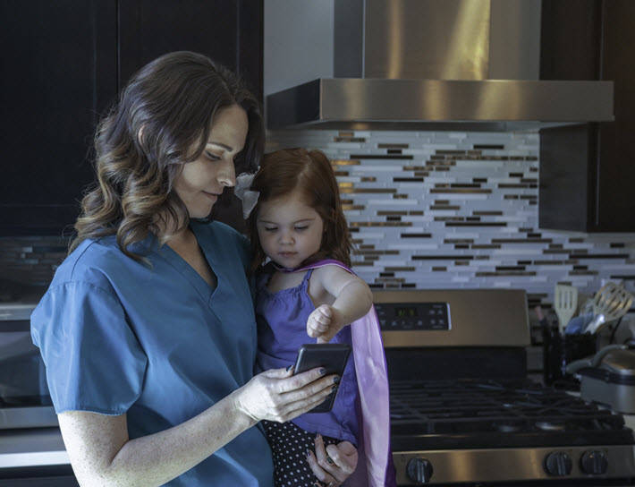 Doctor holding her daughter in her kitchen