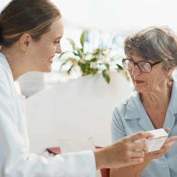Pharmacist explains medication to senior woman