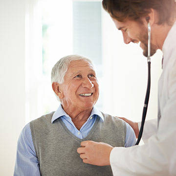 Doctor examining man with stethoscope.