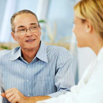 Man smiling and consulting with doctor