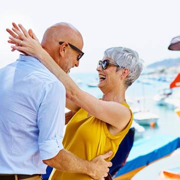 Senior couple embracing at pier