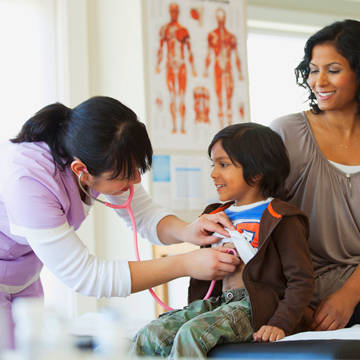 Provider examining young boy at clinic