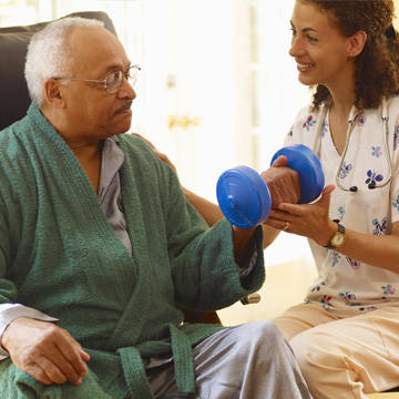 Man in robe doing dumbbell exercises with nurse