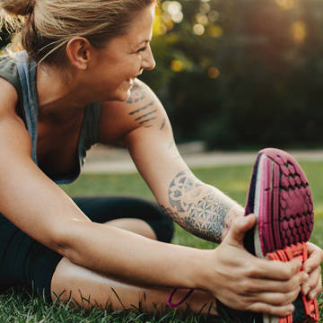 Woman stretching legs in park